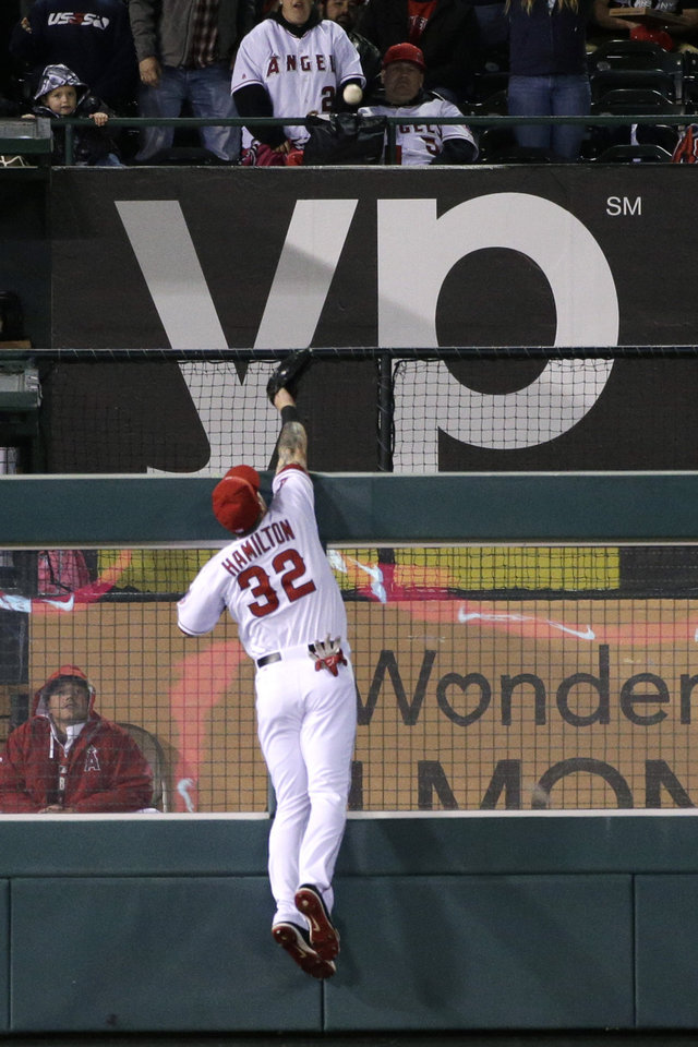 Photo - Los Angeles Angels left fielder Josh Hamilton can't catch a three-run home run hit by Seattle Mariners' Mike Zunino during the sixth inning of a baseball game Wednesday, April 2, 2014, in Anaheim, Calif. (AP Photo/Jae C. Hong)