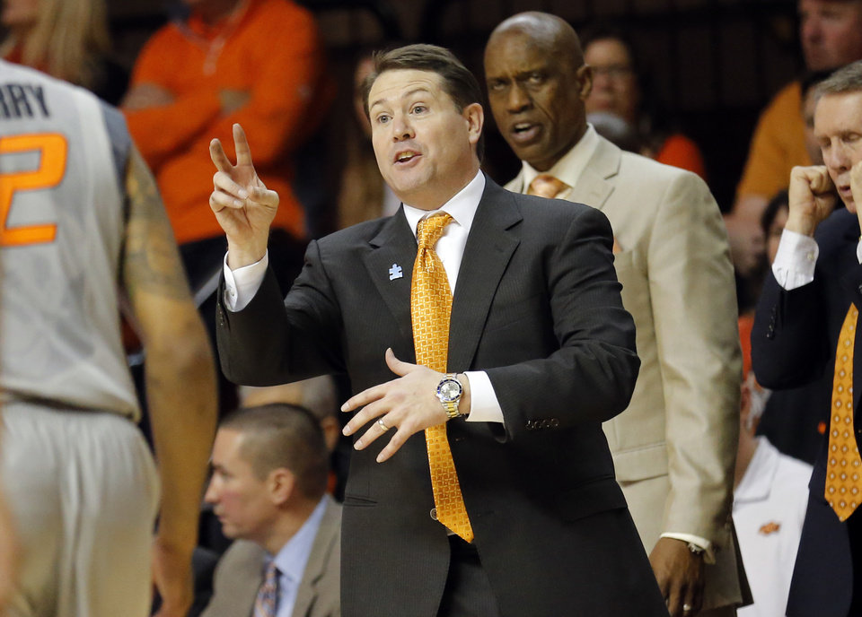 Photo - Oklahoma State head coach Travis Ford coaches during the men's college basketball game between Oklahoma State University and the University of Kansas at Gallagher-Iba Arena in Stillwater, Okla.,  Saturday, Feb. 7, 2015. OSU won 67-62. Photo by Sarah Phipps, The Oklahoman