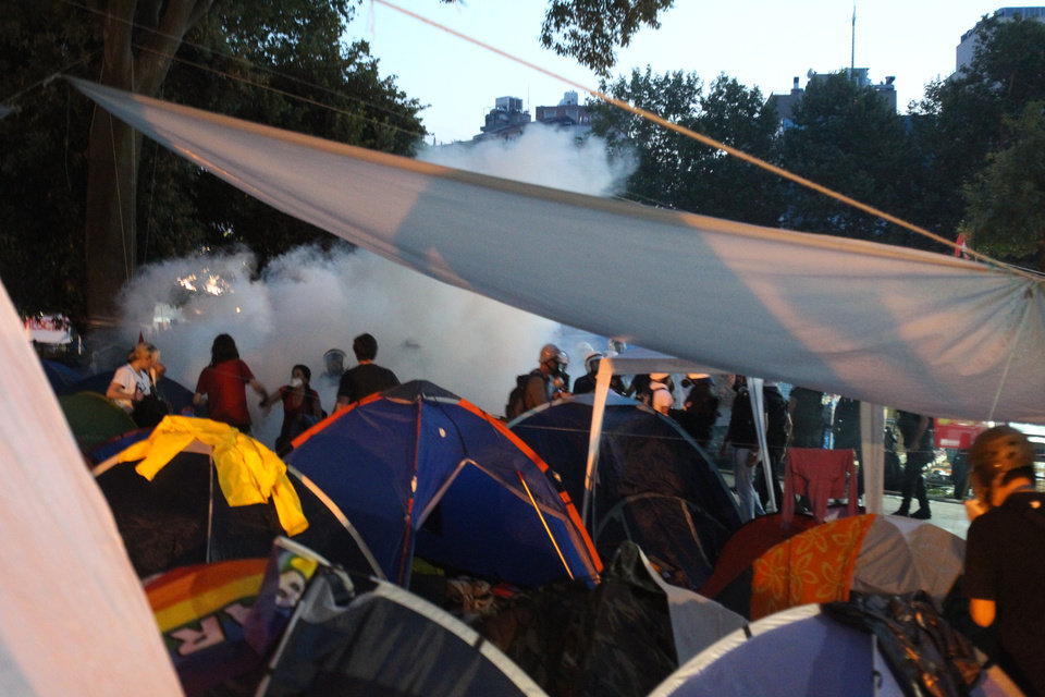 Photo - Police throw tear gas as protestors stand among tents during an  operation to evacuate the Gezi Park of Taksim Square in Istanbul,   Saturday, June 15, 2013.  Protesters will press on with their sit-in at an Istanbul park, an activist said Saturday, defying government appeals and a warning from Prime Minister Recep Tayyip Erdogan for the two-week standoff that has fanned nationwide demonstrations to end. (AP Photo/Thanassis Stavrakis)
