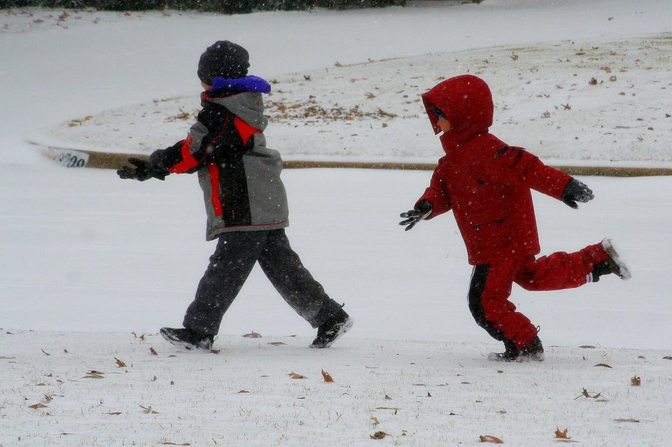 Nathan throws a snowball at Garett in the snow.<br/><b>Community Photo By:</b> Gary Carr<br/><b>Submitted By:</b> Gary, Midwest City