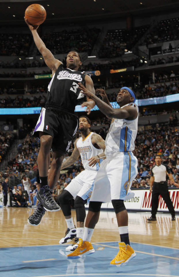 Sacramento Kings guard Aaron Brooks, left, drives the lane for a shot past Denver Nuggets guard Ty Lawson in the first quarter of an NBA basketball game in Denver on Saturday, Jan. 26, 2013. (AP Photo/David Zalubowski)