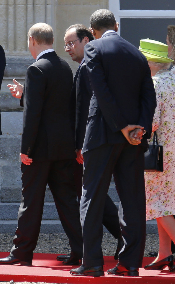Photo - Russian President Vladimir Putin, left, talks to French President Francois Hollande, 2nd left, as they walk next to U.S. President Barack Obama, 2nd right and Britain's Queen Elizabeth after posing for a group photo for the 70th anniversary of the D-Day landings at Benouville castle, in Normandy, France, Friday, June 6, 2014. World leaders and veterans paid tribute on the 70th anniversary of the World War Two D-Day landings to soldiers who fell in the liberation of Europe from Nazi German rule, as host France sought to use the event to achieve a thaw in the Ukraine crisis. (Regis Duvignau, pool)
