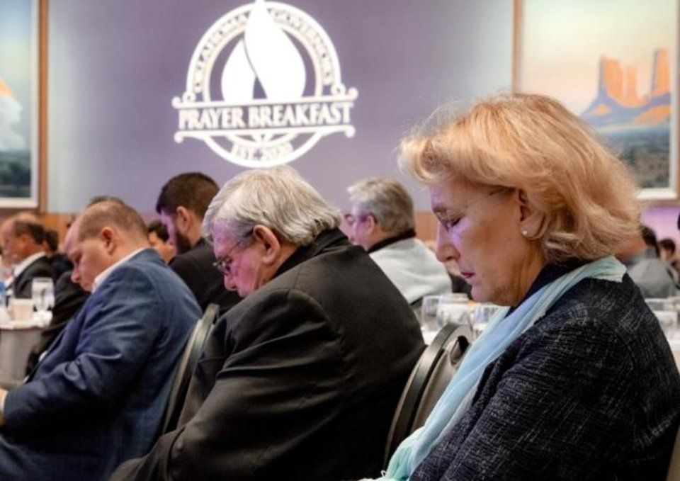 Photo -  Sherri Boyd bows her head in prayer during the Oklahoma Governor's Prayer Breakfast on Tuesday at the National Cowboy and Western Heritage Museum in Oklahoma City. [Chris Landsberger/The Oklahoman]
