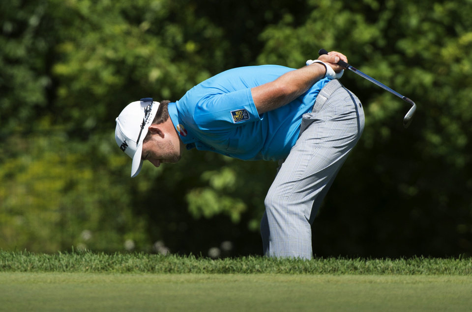 Photo - Graeme McDowell, from Northern Ireland, checks his lie off the sixth green during first-round play at the Canadian Open golf championship on Thursday, July 24, 2014, in Montreal. (AP Photo/The Canadian Press, Paul Chiasson)