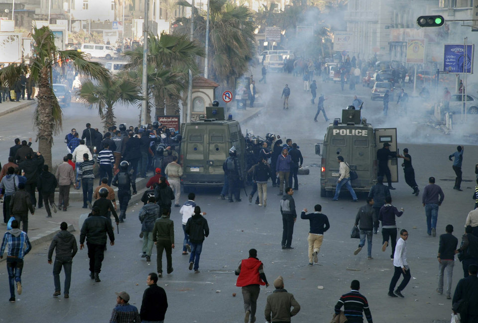 Egyptian police and protesters clash outside a courtroom in Alexandria, Egypt, Saturday, Jan. 19, 2013. Riot police fired tear gas Saturday to disperse demonstrators throwing stones outside an Alexandria courtroom where the city's ex-security director and other officers are on trial for the killing of protesters during Egypt's 2011 uprising. (AP Photo/Ahmed Ramadan)