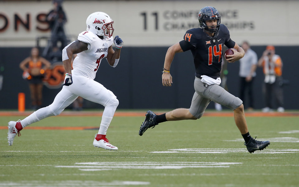 Photo - Oklahoma State's Taylor Cornelius (14) scrambles as he is chased by South Alabama's Sterrling Fisher (9) during a college football game between Oklahoma State (OSU) and South Alabama at Boone Pickens Stadium in Stillwater, Okla., Saturday, Sept. 8, 2018. Photo by Sarah Phipps, The Oklahoman