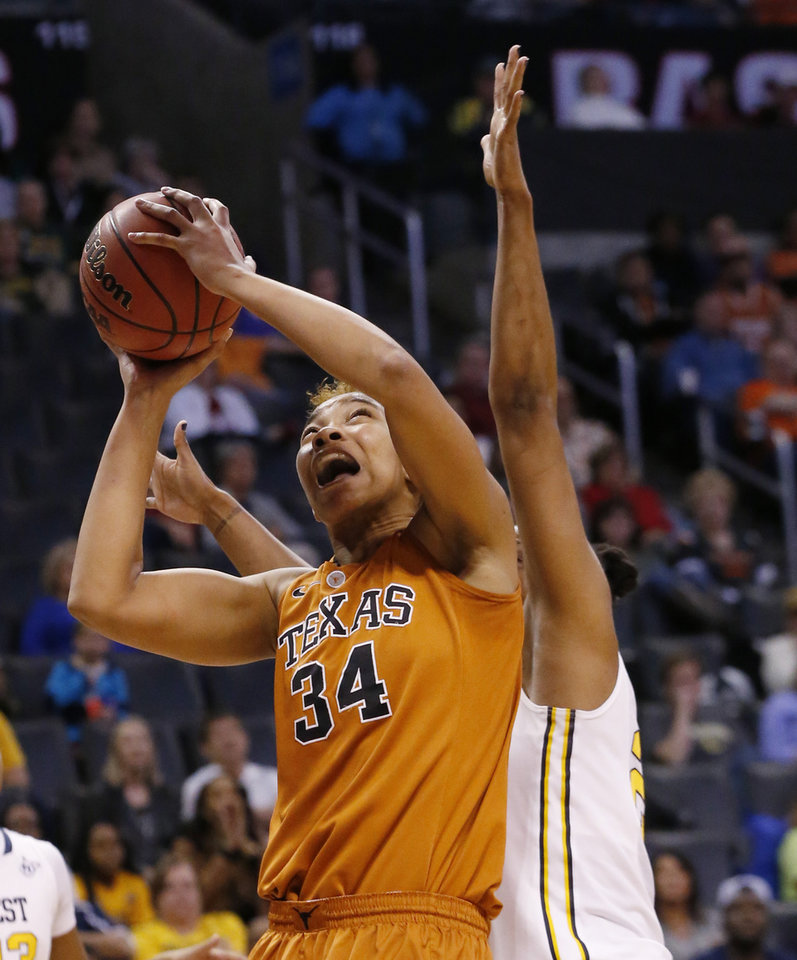 Photo - Texas center Imani McGee-Stafford (34) shoots in front of West Virginia center Asya Bussie in the first half of an NCAA college basketball game in the semifinals of the Big 12 Conference women's tournament in Oklahoma City, Sunday, March 9, 2014. (AP Photo/Sue Ogrocki)