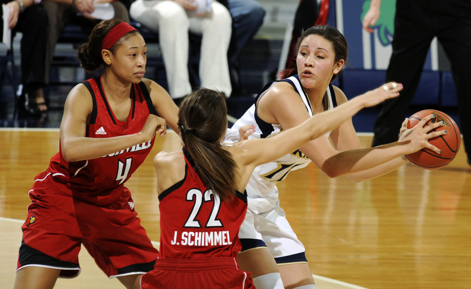 Photo - Notre Dame forward Natalie Achonwa, right, throws a pass around Louisville guards Antonita Slaughter, left, and Jude Schimmel in the first half of an NCAA college basketball game, Monday, Feb. 11, 2013, in South Bend, Ind. (AP Photo/Joe Raymond)