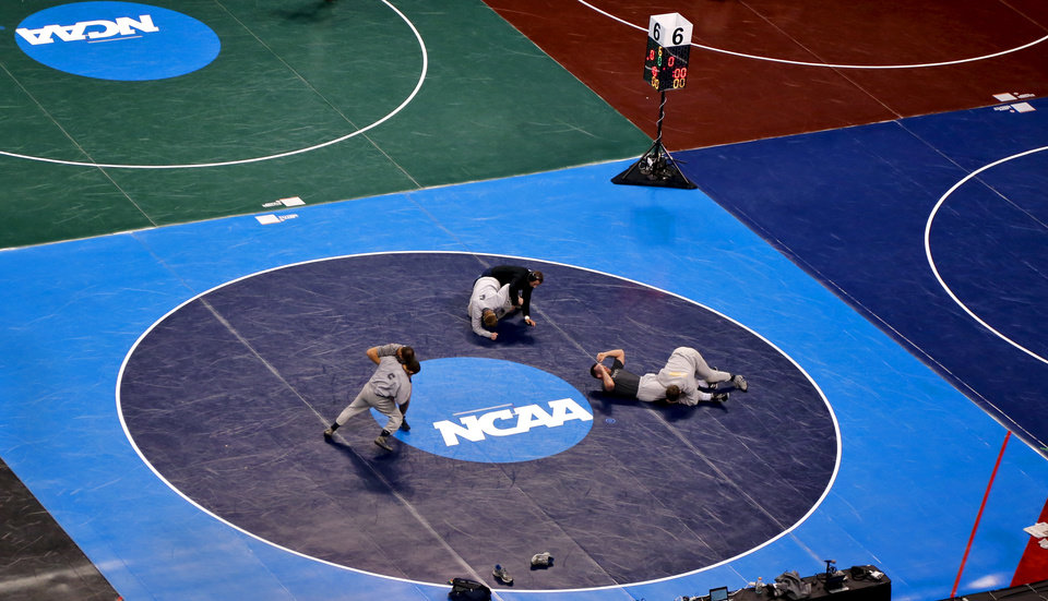 Photo - Wrestlers take to the mats inside the Chesapeake Energy Arena as the get practice before the start of the 2014 NCAA Div. 1 Wrestling Championship in Oklahoma City, Okla. on Wednesday, March 19, 2014. Photo by Chris Landsberger, The Oklahoman