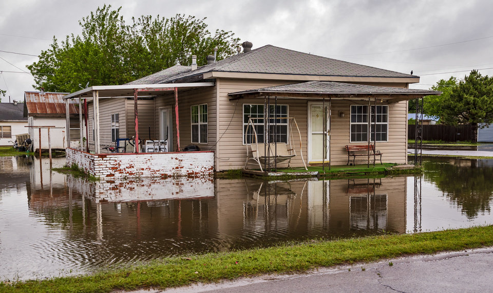 Photo - A home is surrounded by flood waters after  heavy rains flooded areas  in El Reno, Okla. on Tuesday, May 21, 2019.  [Chris Landsberger/The Oklahoman]