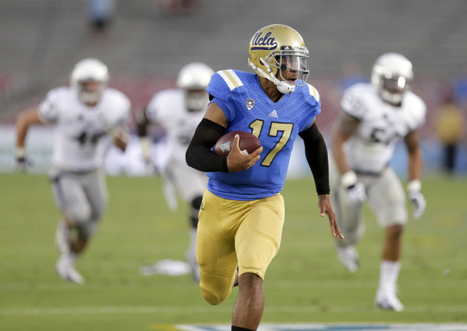 UCLA quarterback Brett Hundley scores on a 37-yard run against Nevada during the first half of an NCAA college football game in Pasadena, Calif., Saturday, Aug. 31, 2013. (AP Photo/Chris Carlson)