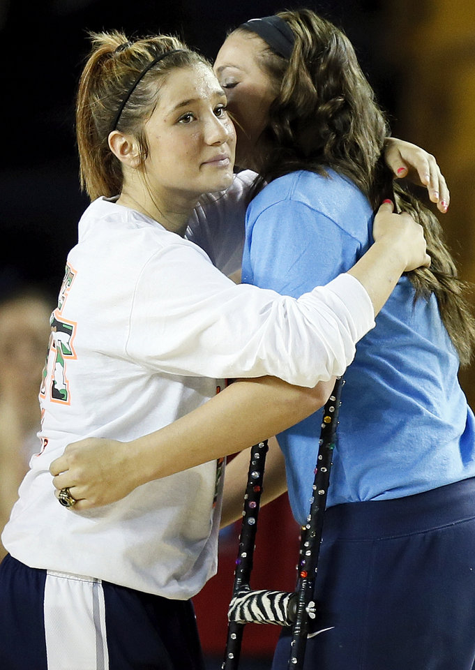 Photo - Shawnee's Bailey Taylor, left, hugs injured teammate McKenzie Cooper during introductions before the Class 5A girls championship high school basketball game in the state tournament at the Mabee Center in Tulsa, Okla., Saturday, March 9, 2013. Taylor wore Coopers' number, 20, in the semifinal and championship games to honor her. Photo by Nate Billings, The Oklahoman
