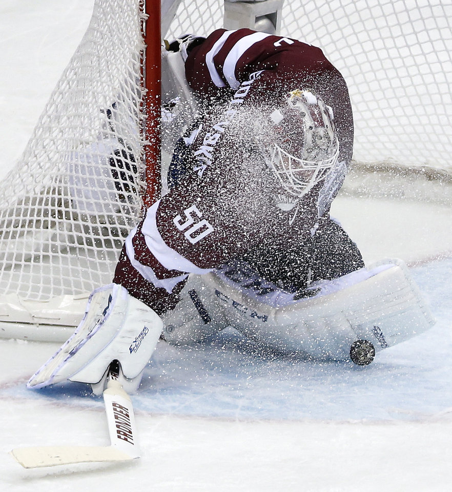 Photo - Latvia goaltender Kristers Gudlevskis blocks a shot by Canada during the second period of a men's quarterfinal ice hockey game at the 2014 Winter Olympics, Wednesday, Feb. 19, 2014, in Sochi, Russia. (AP Photo/Mark Humphrey)