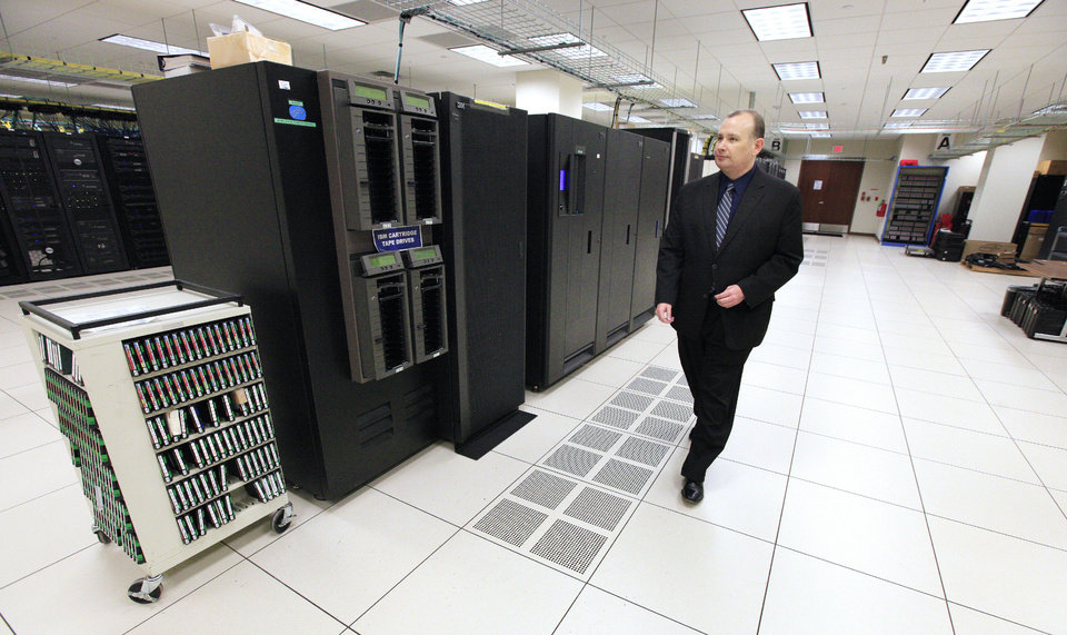 Photo - Mark Gower, chief of security, walks past a row of servers at the State Data Center building in Oklahoma City. Photo by Paul B. Southerland, The Oklahoman  PAUL B. SOUTHERLAND