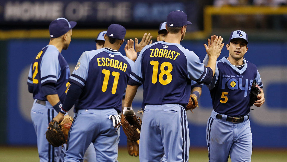 Photo - Members of the Tampa Bay Rays, including Yunel Escobar (11), Ben Zobrist (18) and Sam Fuld (5) celebrate at the end of a baseball game against the Chicago White Sox Saturday, July 6, 2013, in St. Petersburg, Fla. The Rays won 3-0. (AP Photo/Mike Carlson)