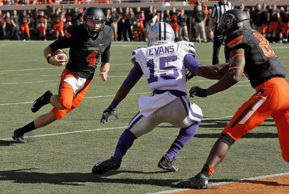 Oklahoma State\'s J.W. Walsh (4) carries the ball on his way to a touchdown near Kansas State\'s Randall Evans (15) and Oklahoma State\'s Jhajuan Seales (81) during a college football game between the Oklahoma State University Cowboys (OSU) and the Kansas State University Wildcats (KSU) at Boone Pickens Stadium in Stillwater, Okla., Saturday, Oct. 5, 2013. Photo by Nate Billings, The Oklahoman