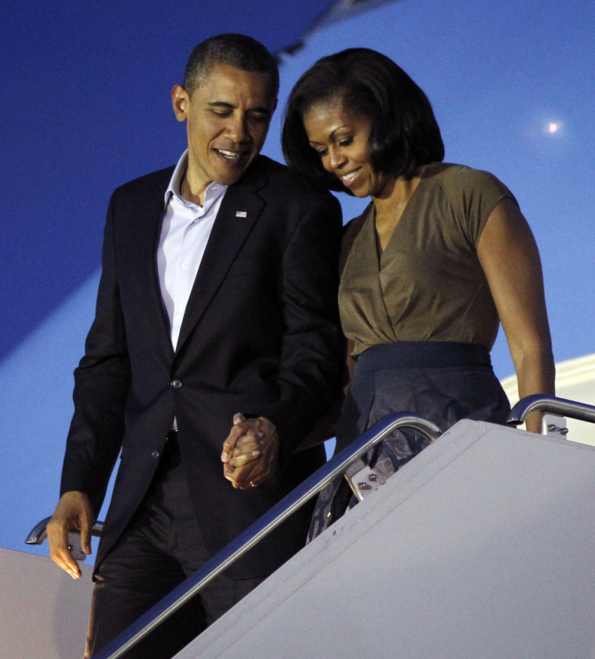 President Barack Obama and first lady Michelle Obama arrive at Chicago O'Hare International airport in Chicago, Saturday, May, 19, 2012. Obama traveled to Chicago to host the two-day NATO summit. (AP Photo/Pablo Martinez Monsivais)