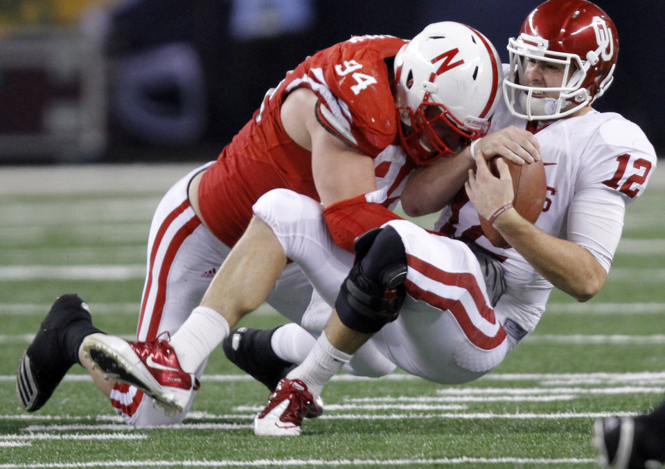 Oklahoma\'s Landry Jones (12) is sacked by Nebraska\'s Jared Crick (94) during the Big 12 football championship game between the University of Oklahoma Sooners (OU) and the University of Nebraska Cornhuskers (NU) at Cowboys Stadium on Saturday, Dec. 4, 2010, in Arlington, Texas. Photo by Chris Landsberger, The Oklahoman