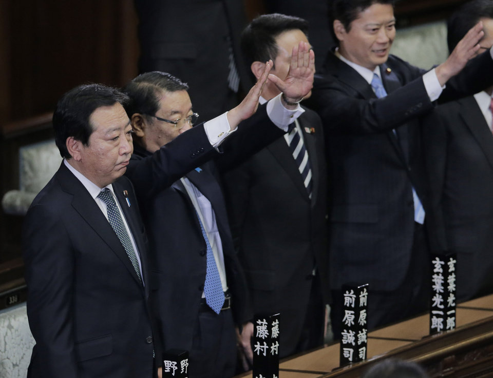 ADDS WHAT PEOPLE DO - Prime Minister Yoshihiko Noda stands still as Chief Cabinet Secretary Osamu Fujimura, second left, and Foreign Minister Koichiro Gemba, right, raise hands and shout banzai, or long live, after he dissolved the lower house of parliament in Tokyo Friday, Nov. 16, 2012. Noda dissolved the lower house of parliament Friday, paving the way for elections in which his ruling party will likely give way to a weak coalition government divided over how to solve Japan's myriad problems. (AP Photo/Koji Sasahara)