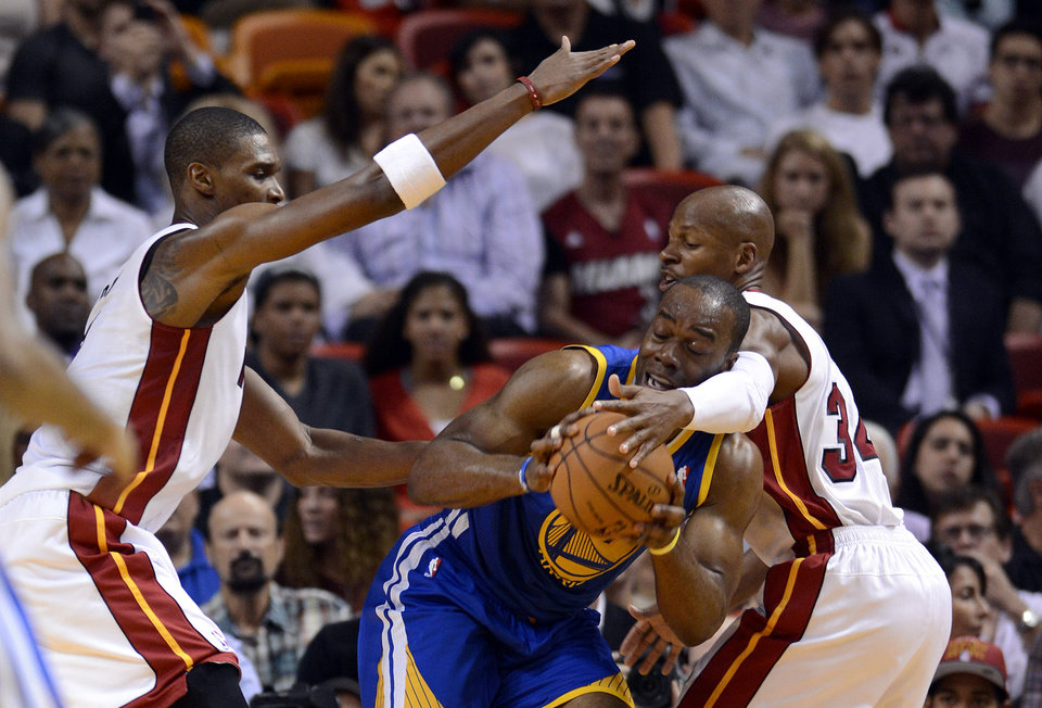 Golden State Warriors\' Carl Landry, center, is defended by Miami Heat Chris Bosh,left, and Ray Allen (34) during an NBA basketball game on Wednesday, Dec, 12, 2012, in Miami. (AP Photo/Rhona Wise)
