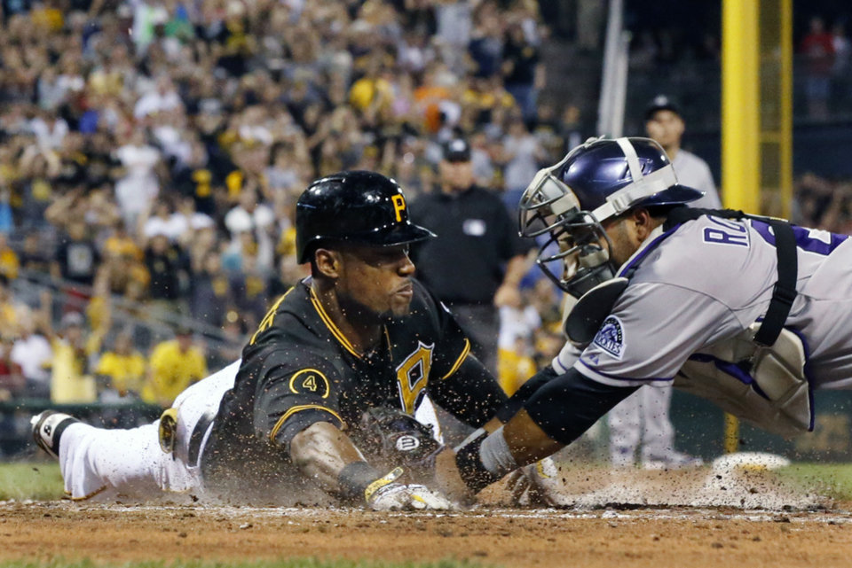Photo - Pittsburgh Pirates' Starling Marte, left, is tagged out attempting an inside the park home run by Colorado Rockies catcher Wilin Rosario during the sixth inning of a baseball game in Pittsburgh Friday, July 18, 2014. Marte drove in a run on the play. (AP Photo/Gene J. Puskar)