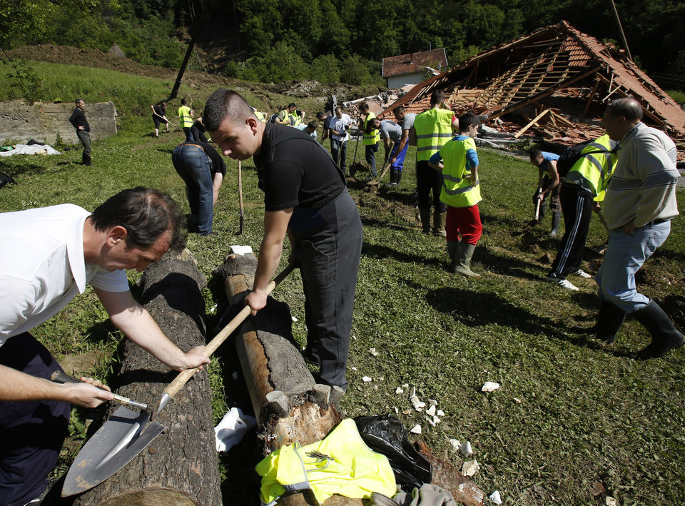 Photo - Bosnian volunteers work to save the remains of a village after a landslide near Tuzla, 140 kms north of Sarajevo, on Monday May 19, 2014. Three months' worth of rain fell on the Balkan region in three days, producing the worst floods since rainfall measurements began 120 years ago. (AP Photo/Amel Emric)
