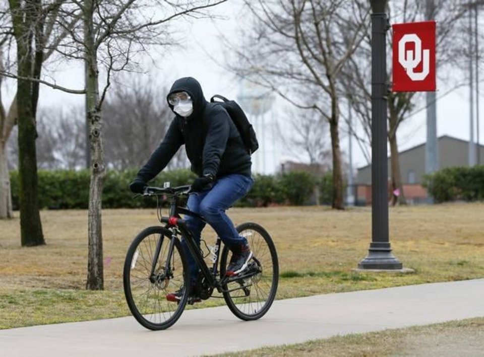 Photo -  A cyclist wears a mask and googles while riding north on a sidewalk along Jenkins Avenue on the University of Oklahoma campus in Norman on Tuesday. [Nate Billings/The Oklahoman]