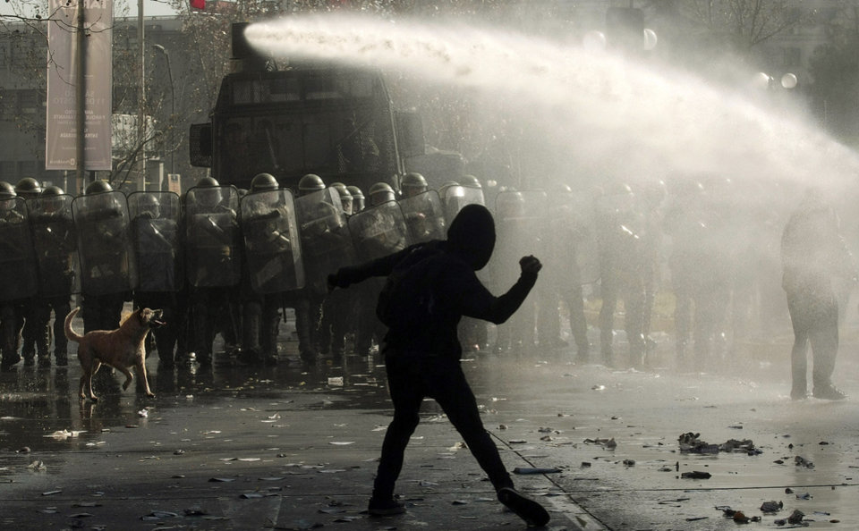 Photo -   Police uses water canons as a demonstrator hurls a stone during a march demanding free education in Santiago, Chile, Wednesday, Aug. 8, 2012. Police used water cannons and tear gas to break up the protest and three buses were set ablaze.(AP Photo / Luis Hidalgo)