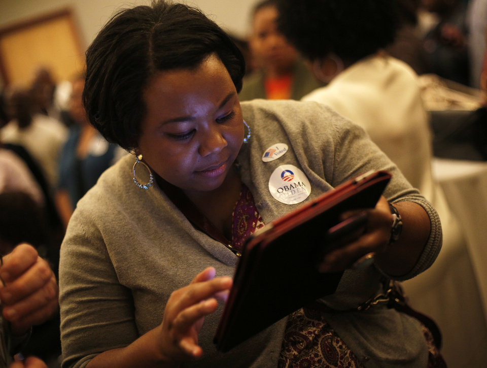 Photo - Tamya Cox looks at election results Tuesday on her iPad during the Oklahoma Democratic Party watch gathering at the Reed Center in Midwest City.  Photo by Garett Fisbeck, The Oklahoman  GARETT FISBECK