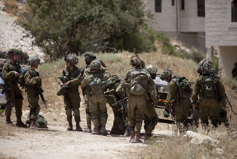 Photo - Israeli soldiers take a break during a military operation to search for three missing teenagers outside the West Bank city of Hebron, Monday, June 16, 2014. Israeli troops on Monday rounded up dozens more senior Hamas activists and killed a Palestinian in a clash with stone throwers — part of a feverish search for three kidnapped Israeli teenagers who Israel alleges were seized by the Islamic militant group. (AP Photo/Majdi Mohammed)