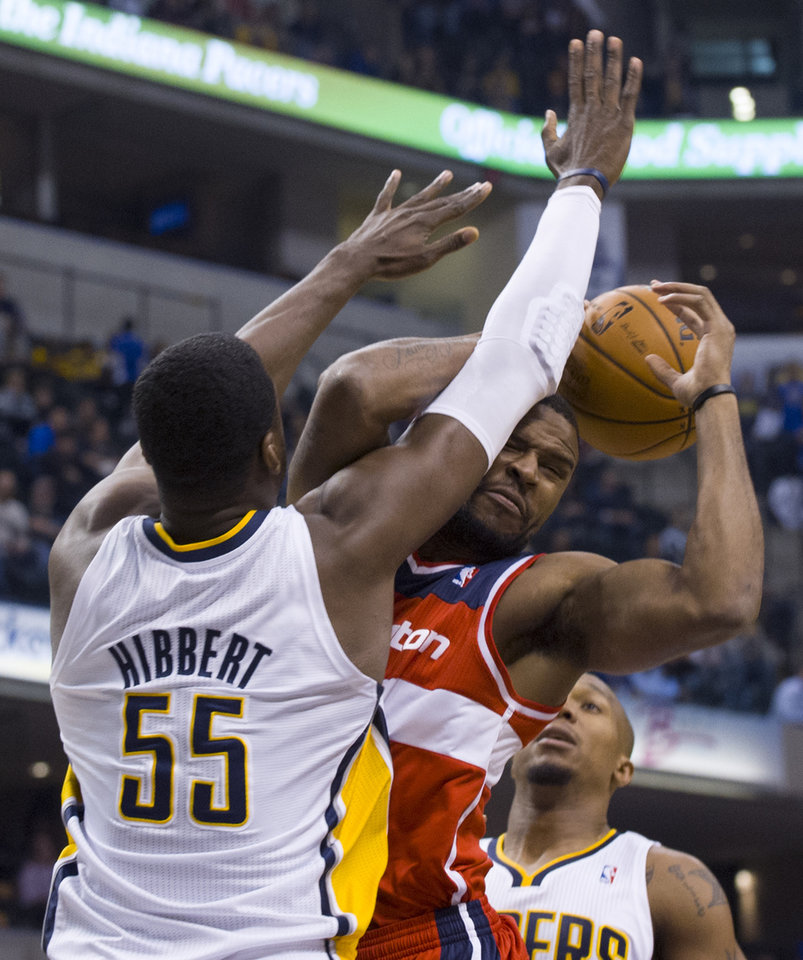 Indiana Pacers center Roy Hibbert (55) puts a stop to the drive in the lane by Washington Wizards\' power forward Trevor Booker during first-half action in an NBA basketball game in Indianapolis, Saturday, Nov. 10, 2012. (AP Photo/Doug McSchooler)