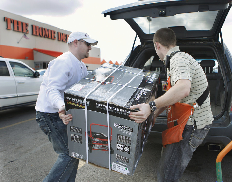 Photo - SNOW / ICE / PREPARE / PREPARATION: Terry Burton, Piedmont resident, loads a generator with the help of Norman Home Depot employee Darren Parmele in preparation for an approaching winter storm on Wednesday,  Jan. 27, 2010, in Norman, Okla.  Burton used his phone to locate the generator when stores in his area sold out.  Photo by Steve Sisney, The Oklahoman ORG XMIT: KOD