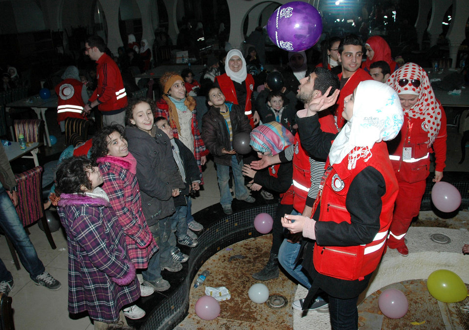 Photo - In this photo taken on Sunday Feb. 9, 2014, and released by the Syrian official news agency SANA, Syrian Arab Red Crescent members in red uniforms play with children as they wait to get on a bus to evacuate the battleground city of Homs, Syria. A Syrian Red Crescent official says around 300 more people were evacuated Monday from besieged rebel-held neighborhoods of Syria's third-largest city, Homs. (AP Photo/SANA)