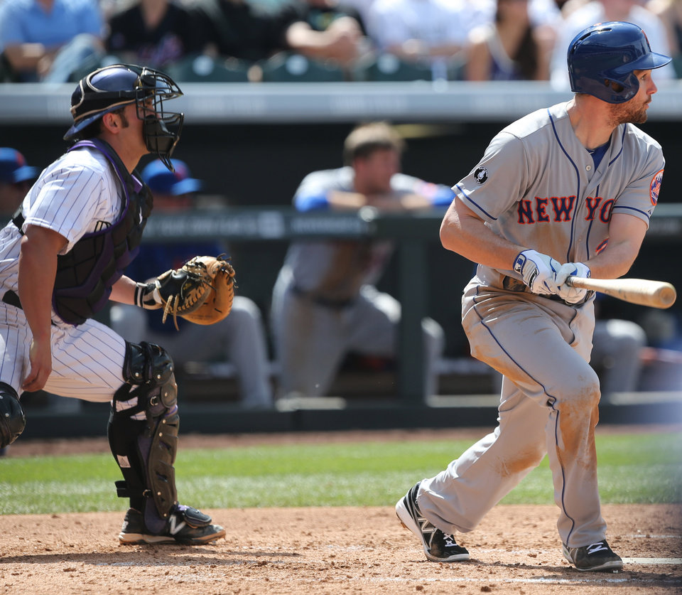Photo - New York Mets' Daniel Murphy, right, follows the flight of his RBI-double with Colorado Rockies catcher Michael McKenry in the fourth inning of a baseball game in Denver on Sunday, May 4, 2014. (AP Photo/David Zalubowski)