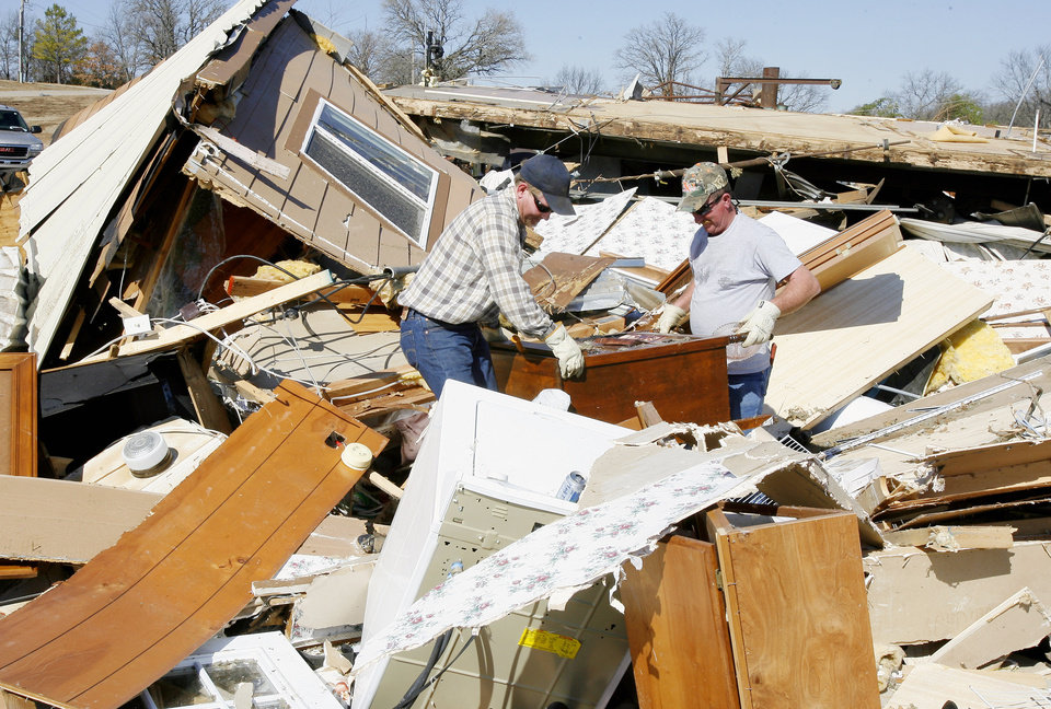 Photo - Roger Jones, right, gets help searching the debris of his mobile home from his nephew Josh Jones, left, on Newport Road in Lone Grove, Wednesday, Feb. 11, 2009. BY PAUL B. SOUTHERLAND, THE OKLAHOMAN