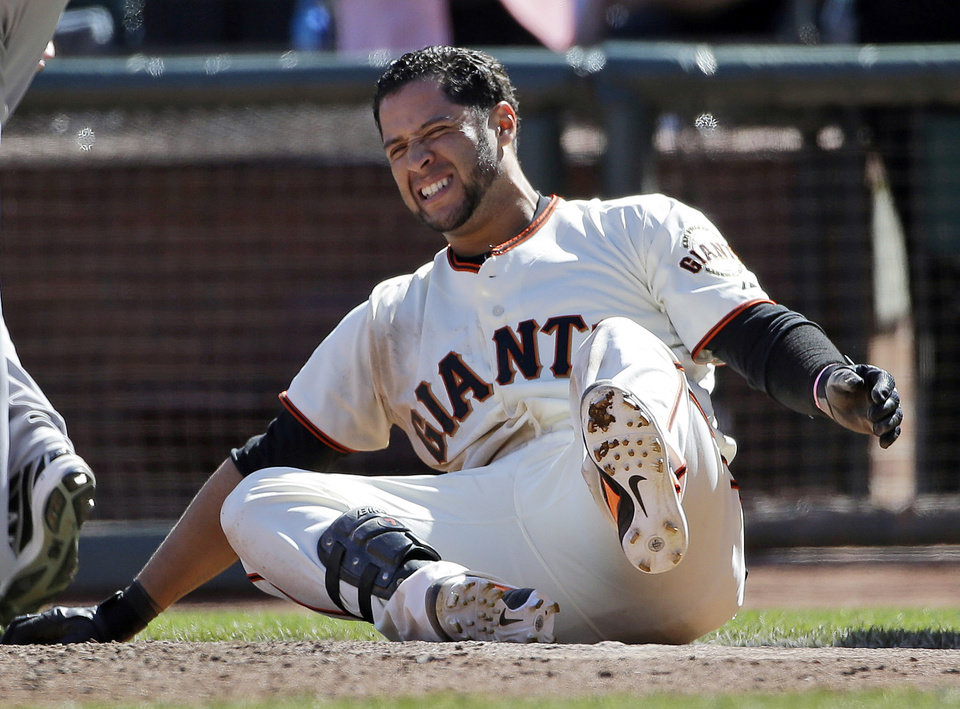Photo - San Francisco Giants' Gregor Blanco grimaces after being tagged out at the plate as he tried for an inside-the-park home run during the ninth inning of a baseball game against the Colorado Rockies on Sunday, April 13, 2014, in San Francisco. San Francisco won 5-4. (AP Photo/Marcio Jose Sanchez)