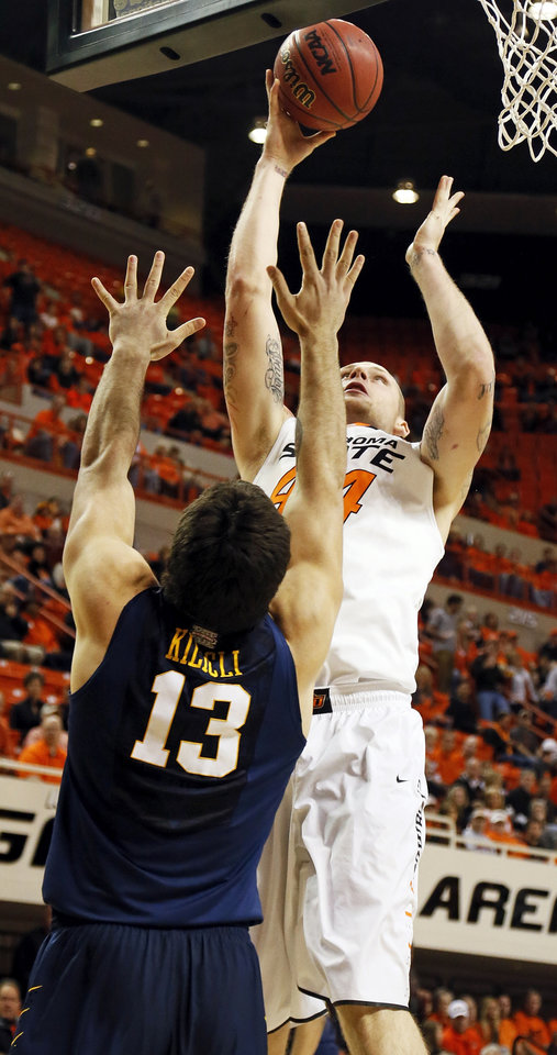 Oklahoma State's Philip Jurick (44) shoots against West Virginia's Deniz Kilicli (13) during an NCAA men's basketball game between Oklahoma State University (OSU) and West Virginia at Gallagher-Iba Arena in Stillwater, Okla., Saturday, Jan. 26, 2013. Photo by Nate Billings, The Oklahoman