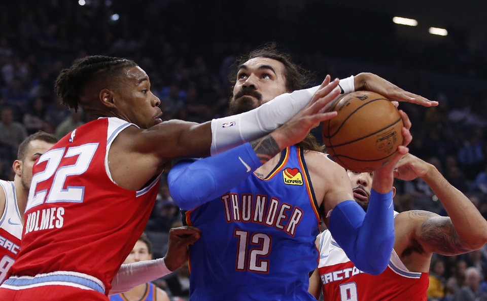 Photo - Sacramento Kings forward Richaun Holmes, left, blocks the shot of Oklahoma City Thunder center Steven Adams during the first quarter of an NBA basketball game in Sacramento, Calif., Wednesday, Dec. 11, 2019. (AP Photo/Rich Pedroncelli)
