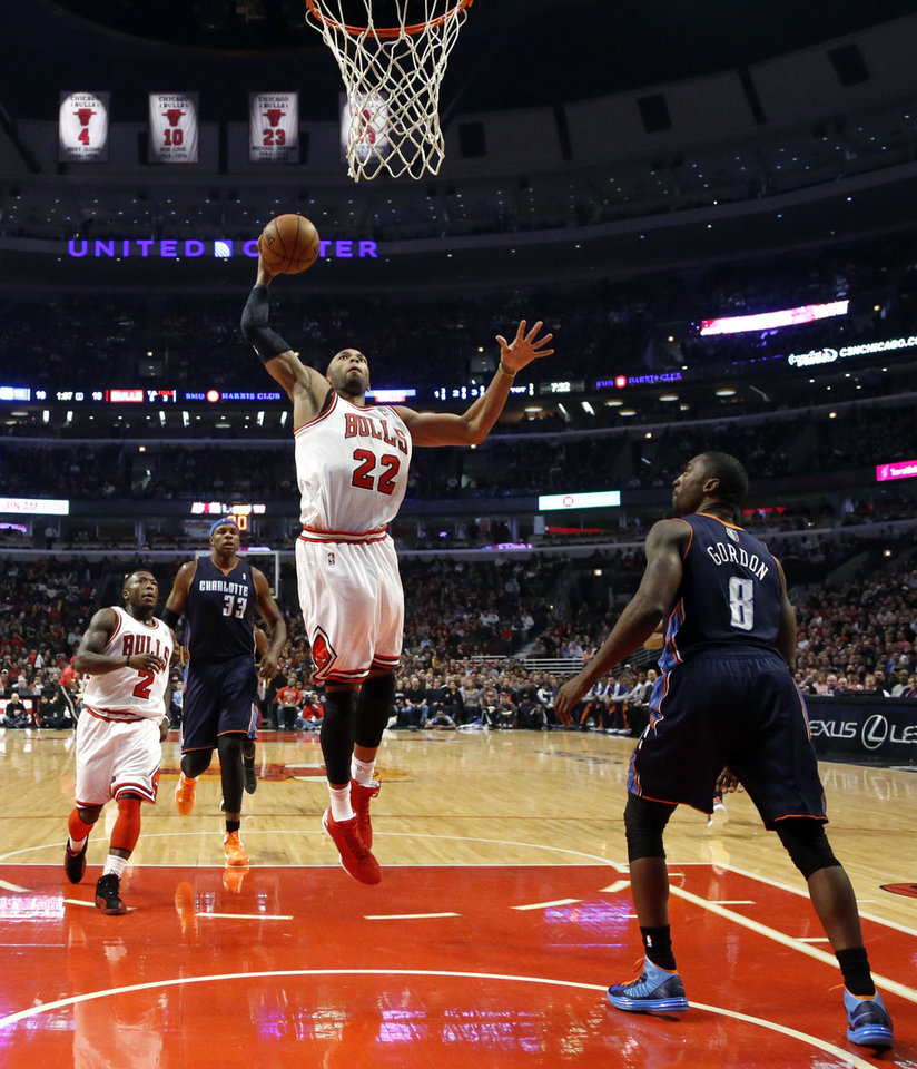 Photo - Chicago Bulls' Taj Gibson (22) goes up for a dunk as Nate Robinson (2) and Charlotte Bobcats' Brendan Haywood (33) and Ben Gordon watch during the first half of an NBA basketball game, Monday, Jan. 28, 2013, in Chicago. (AP Photo/Charles Rex Arbogast)