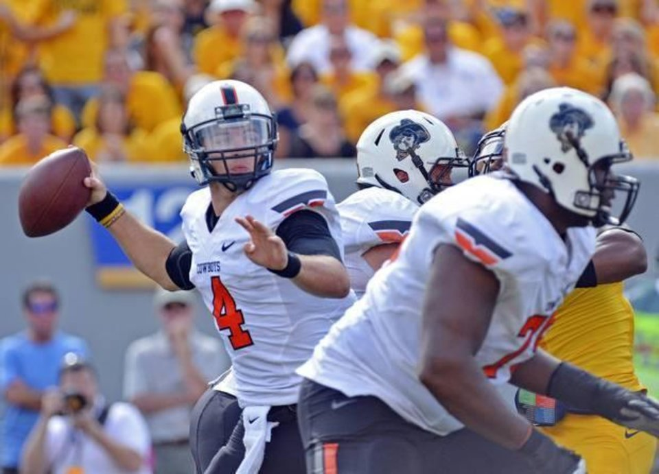 Photo - Oklahoma State Quarterback J.W. Walsh (4) attempts a pass during the third quarter of an NCAA college football game against West Virginia in Morgantown, W.Va., on Saturday, Sept. 28, 2013. (AP Photo/Tyler Evert)
