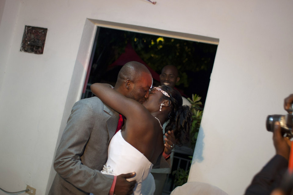 Photo - In this July 20, 2012 photo, professional dancer Georges Exantus kisses his wife Sherly Henrisme Exantus on their wedding night in Port-au-Prince, Haiti. The earthquake three years ago in Haiti's capital flattened the apartment where Georges Exantus was living and he spent three days trapped under a heap of jagged rubble. After friends dug him out, doctors amputated his right leg just below the knee. Three years later, the 32-year-old professional dancer is back on the floor, spinning away as he does the salsa, cha-cha and samba. A prosthetic leg doesn't hold him back. (AP Photo/Dieu Nalio Chery)