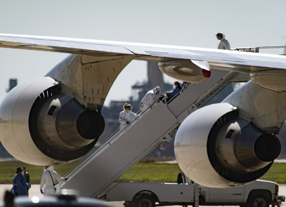 Photo -  In this Friday, Feb. 7, 2020 photo, a passenger is helped off of a chartered 747 that arrived from Wuhan, China at Joint Base San Antonio-Lackland, in Texas. U.S. officials on Thursday, Feb. 13, announced the country's 15th confirmed case of the new coronavirus — an evacuee from China who had been transported on this flight and was under quarantine in Texas. The patient is now in isolation at a hospital and was reported in stable condition. (Billy Calzada/The San Antonio Express-News via AP)