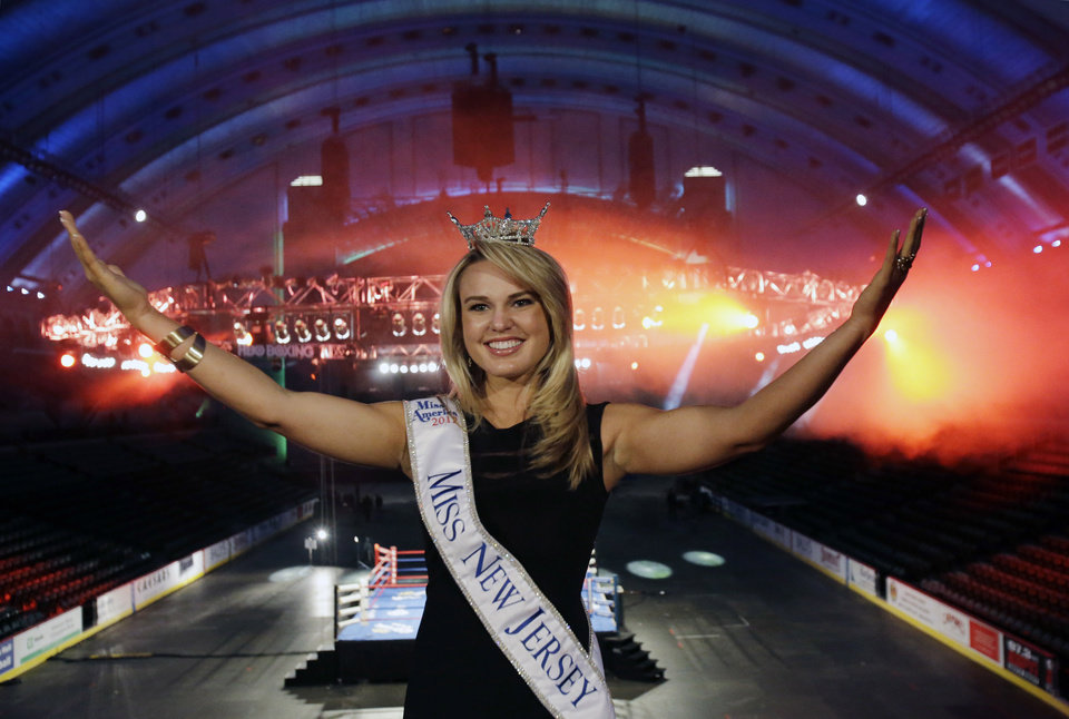 Photo - Miss New Jersey for 2012 in the Miss America pageant, Lindsey Petrosh, of Egg Harbor City, N.J., gestures for photographs in Atlantic City's Boardwalk Hall, Thursday, Feb. 14, 2013, in Atlantic City, after New Jersey Lt. Gov. Kim Guadagno announced that the Miss America pageant is returning to Atlantic City. The pageant returns to Atlantic City in September after spending six years in Las Vegas. (AP Photo/Mel Evans)