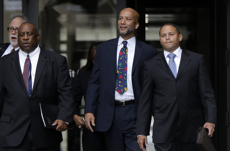 Photo - Former New Orleans Mayor Ray Nagin, center, leaves federal court after being sentenced in New Orleans, Wednesday, July 9, 2014. Nagin was sentenced to 10 years in prison for bribery, money laundering and other corruption that spanned his two terms as mayor, including the chaotic years after Hurricane Katrina hit in 2005. He was convicted Feb. 12 of accepting hundreds of thousands of dollars from businessmen who wanted work from the city or Nagin's support for various projects. The bribes came in the form of money, free vacations and truckloads of free granite for his family business. (AP Photo/Gerald Herbert)