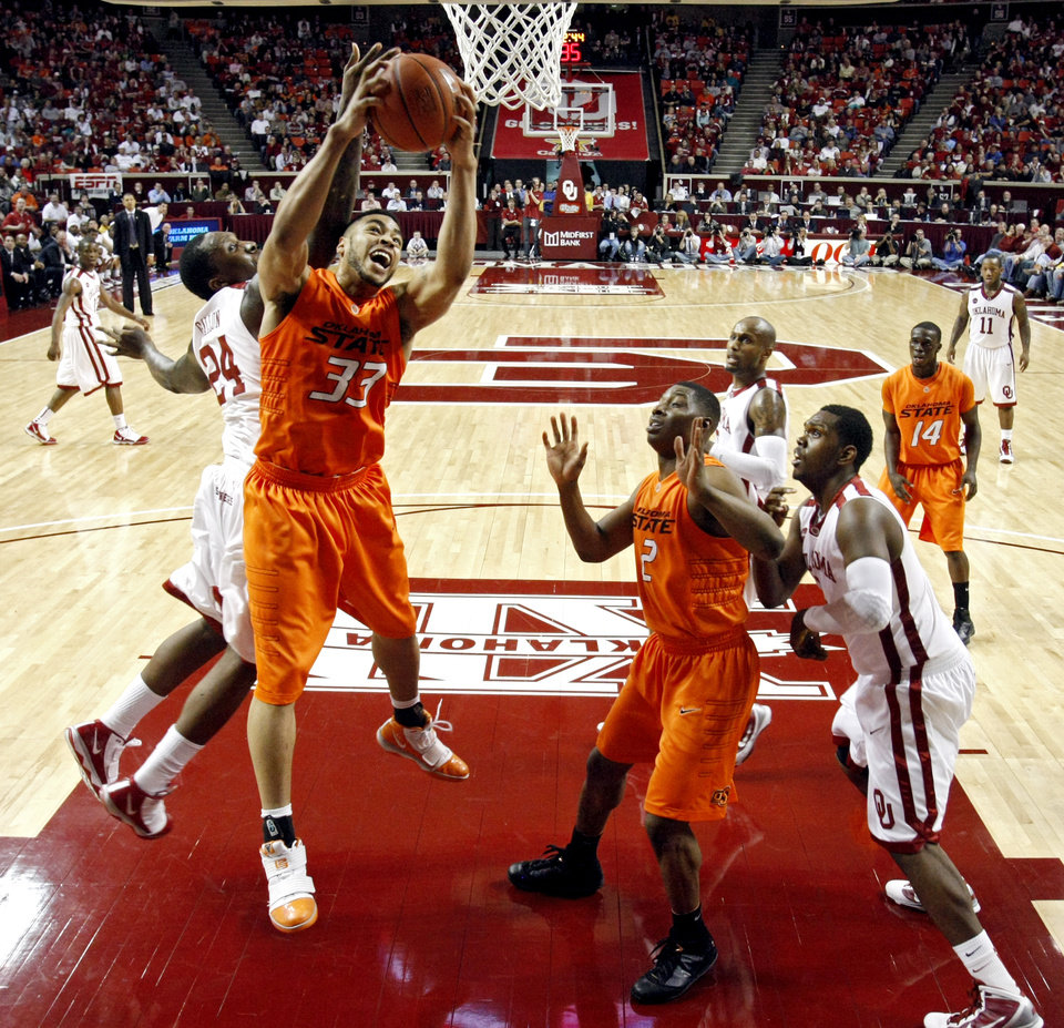 Photo - OSU's Marshall Moses (33) pulls in a rebound over OU's Tiny Gallon (24) during the first half of the college bedlam basketball game between The University of Oklahoma Sooners (OU) and Oklahoma State University University Cowboys (OSU) at the Lloyd Noble Center on Monday, Jan. 11, 2010, in Norman, Okla.