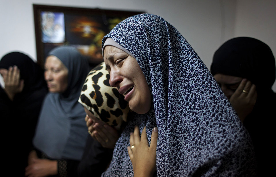 Photo - Female relatives of slain Palestinian Ahmad Arafat Sabarin, 20, who was killed by Israeli army fire early Monday during a confrontation between stone throwers and soldiers, cries with a relative at the family house, prior to his funeral procession in the Palestinian refugee camp of Jalazoun, at the outskirts of the West Bank city of Ramallah, Monday, June 16, 2014. Israeli troops on Monday rounded up dozens more senior Hamas activists and killed a Palestinian in a clash with stone throwers — part of a feverish search for three kidnapped Israeli teenagers who Israel alleges were seized by the Islamic militant group. (AP Photo/Nasser Nasser)