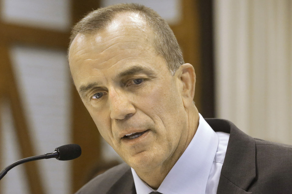 Photo - Jim Ross, manager, Division of Air Pollution Control at State of Illinois, testifies during an Illinois Commerce Commission hearing Monday, Aug. 18, 2014, in Springfield, Ill. The Illinois Commerce Commission is holding hearings on how to reduce the state's global warming pollution. Monday's meeting is the first of three to determine how to meet tougher federal limits on greenhouse gases. It's part of a sweeping initiative to curb carbon dioxide emitted by the nation's power plants 30 percent by 2030. (AP Photo/Seth Perlman)