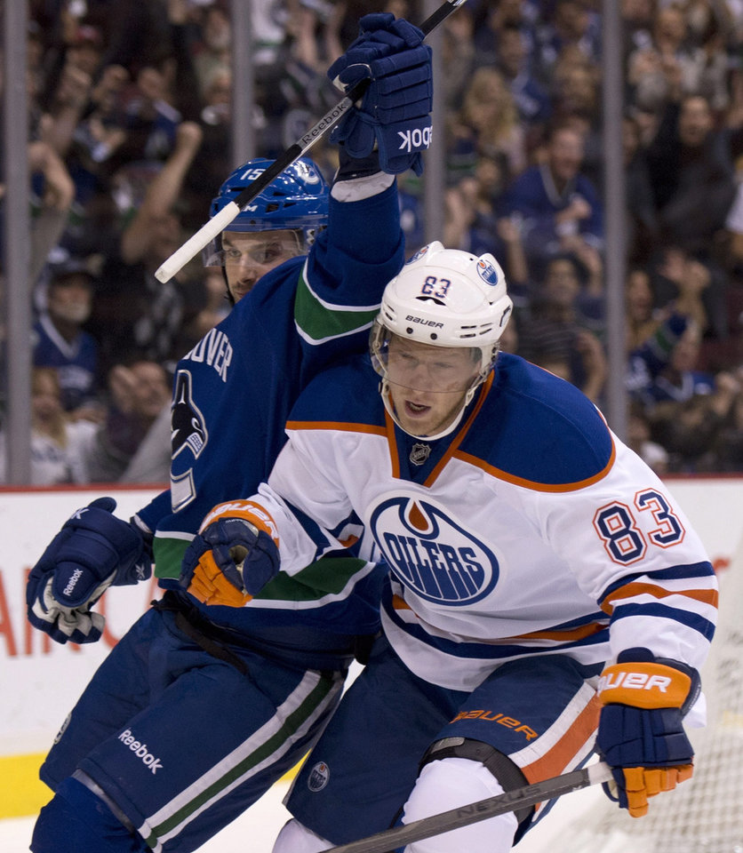 Photo - Vancouver Canucks center Brad Richardson (15) celebrates his goal as Edmonton Oilers right wing Ales Hemsky (83) skates past during the first period of an NHL hockey game in Vancouver, British Columbia, Saturday, Oct. 5, 2013. (AP Photo/The Canadian Press, Jonathan Hayward)