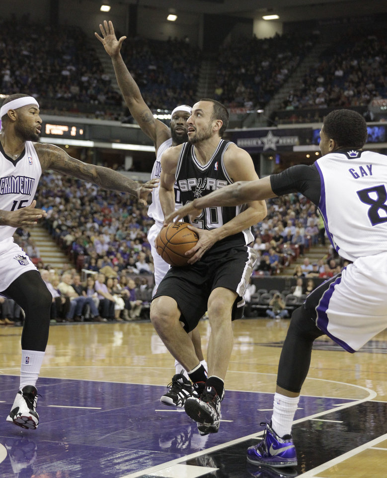 Photo - San Antonio Spurs guard Manu Ginobili, center, of Brazil, drives to the basket between Sacramento Kings' DeMarcus Cousins, left, Reggie Evans, second from right and Rudy Gay during the first quarter of an NBA basketball game in Sacramento, Calif., Friday, March 21, 2014.(AP Photo/Rich Pedroncelli)