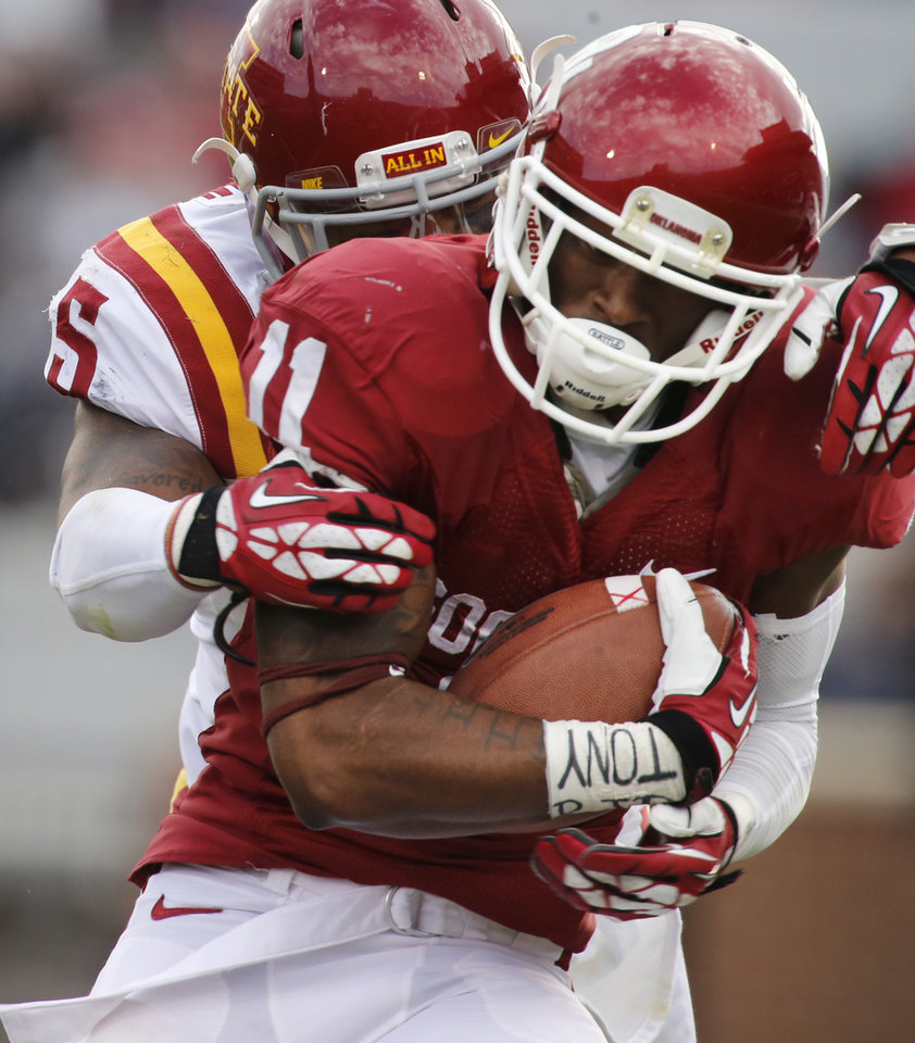 Photo - Oklahoma Sooner's Lacoltan Bester (11) catches a long pass in front of Jacques Washington (5) during the second half of the college football game between the University of Oklahoma Sooners (OU) and the Iowa State University Cyclones (ISU) at Gaylord Family-Oklahoma Memorial Stadium in Norman, Okla. on Saturday, Nov. 16, 2013. Photo by Steve Sisney, The Oklahoman